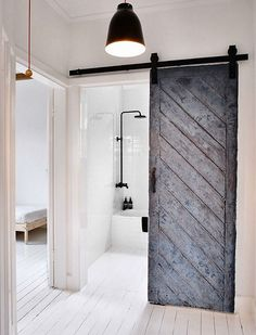 The old barn door that leads into the bathroom is so pretty and adds some roughness to this clean, white house Bathroom. WABI SABI Scandinavia - Design, Art and DIY...