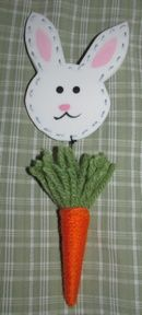 Rabbit cut from foam board and painted.  Carrot made from yarn and hung from rabbit.  Pin glued on back of rabbit.