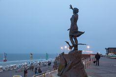 """Selbst an diesigen Abenden sind immer noch ein paar Spaziergänger auf der Kurpromenade unterwegs. Seit 1990 steht in ihrer Mitte die Bronzeskulptur """"S.O.S. – Save our Seas"""", die zu einem schonenderen Umgang mit der Umwelt aufruft."""
