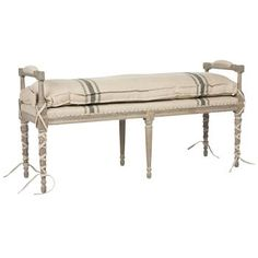 Extend a warm, French Country welcome with this oversized weathered wood bench in your entryway or end of bed. Light grey, layered with white and cream ballet ties, highlights the unique features of the framework. Six tapered legs and two padded arms surround the elongated seat. A simple, striped natural linen cushion can be attached for extra comfort and plush polish.