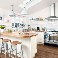 lovely bright kitchen.  perfect size.  nice mix of white and wood. hanging lights over island.