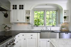 White kitchen with soapstone countertops around the peripheral and marble countertops on the island