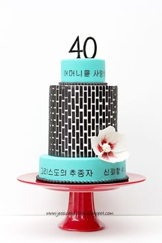I made this cake for a sweet sweet friend of mine turning 40!  The Korean characters I painted around the top and bottom tier say things like, Beautiful Woman, Devoted Wife, Loving Mother, etc.  It was chocolate mudcake with chocolate ganache.  The black pattern is modeling chocolate.  The flower is inspired by the Rose of Sharon...the Korean national flower and her wedding flower.  Her favorite colors are turquoise, red and black.  This cake was featured in Cake Central Magazine last month.  Th
