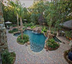 Backyard Swimming Pool With Shrubs And Pavers