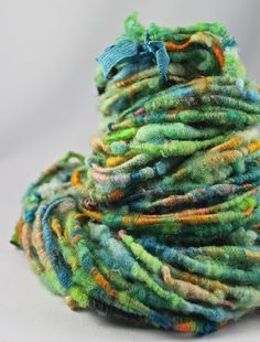 This art yarn was corespun from my own hand dyed Cormo in greens and blues. To this I added some lovely merino, silk, faux cashmere, bamboo and a
