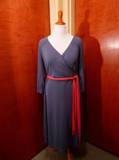 Wearing this plus size gray true wrap dress with it's pink belt and inseam pockets, you are ready for your life all day and night!
