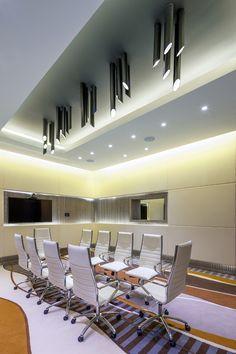 Tubes of matt black brass - light fixture for a boardroom of technical appearance.