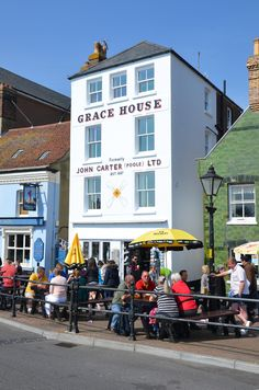 Our shop on Poole Quay, with members of the public sitting outside, catching the sun, soaking up the atmosphere and drinling wine and beer before building up the courage to enter Grace House with their purses and wallets more than half full!