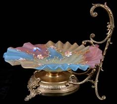 """Thomas Webb and Sons English Victorian art glass bride\'s basket.  Rainbow stained and satin finish crimped glass bowl with enamel florals and butterly on gilt metal ornate handled base.  Circular acid stamp \""""Thomas Webb and Sons\"""" located underside of bowl surrounding hole for screw mount. Bowl 10\"""" diameter, metal handle 10\"""" tall.  Very good condition."""