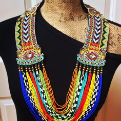 A bold beaded necklace with Tribal flair that really makes a statement! Hundreds of glass seed beads, brass and silver metal beads are hand-loomed