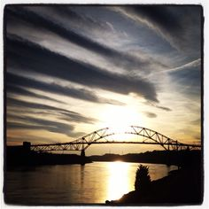 Sky Art- striped golden sky over Cape Cod canal, Sagamore Bridge in background