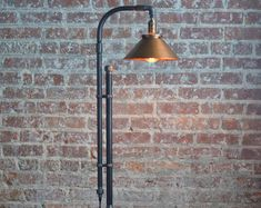 This floor lamp combines rustic copper in an industrial style fixture. The squirrel cage edison bulbs reflect off the copper to provide a brilliant amber glow. This fixture uses key turn nickel sockets that can be switched on and off independently. The 60 filament bulbs are included with the purchase. The form of the fixture is created using industrial black iron piping. A retro style cloth covered cord and plug provide power to the lamp. The base is created using reclaimed wood and a heavy…