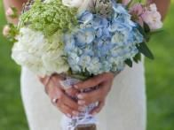 Blue hydrangea , white hydrangea, pink spray roses, peach spray roses, Queen Anne's lace, echeveria and seed eucalyptus are wrapped in burlap with an overlay of white satin lace ribbon and a personal charm attached in this floral design by  The Tangled Vine Designs