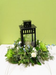 Wedding centerpieces with lanterns in the middle, featuring roses, delphinium and fuji mums with assorted greenery. www.jandaflorist.com #centerpiece #weddingflowers #lantern #delphinium