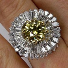 """A breathtaking """"ballerina"""" estate ring circa 1950s with a 4.50 carat fancy deep yellow round brilliant and white baguette-cut diamonds."""