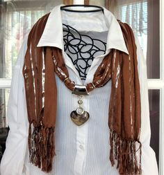 Elegant scarf is a solid brown with silver threads. The pendant is an acrylic swirl patterned heart. Scarf is 70 inches long out of a soft material.