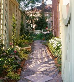 Narrow spaces are popular places to add designed walkways. Here, two sizes of square precast concrete stepping-stones are set on the diagonal to form the base of a corridor through a side yard. Brick edging holds the gravel surrounding the squares in place.