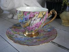 This beautiful vintage Shelley Tea Cup and Saucer on in the Rock Garden pattern. Trimmed and scalloped in gold with lots of pinks,yellows and a touch of green and blue. Very gorgeous and in great condition.