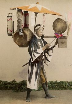 Street seller of sweet-cakes. Hand-colored photo. Late 19th century, Japan