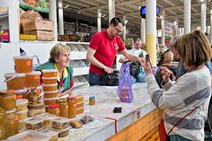 Shopping at the fresh market in Yaroslavl, Russia. This vendor sells locally produced honey ranging, including some still on the beehive.