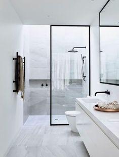 Cuarto de baño en marmol blanco con betas negras y ducha con marco negro