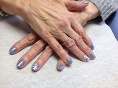Blue with silver glitter and snowflake accent nails  Oasis Salon and Spa Mill Hall Pa (570)726-6565