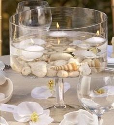 Simple rocks and seashells with floating candles in a clear cylinder vase make a simple but elegant centerpiece