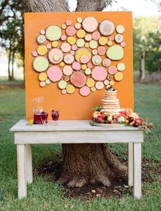 Adorable outdoor cake table display with colorful sliced logs.