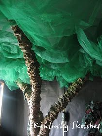 """Tree branches made out of pool noodles and brown packing paper, and the """"leaves"""" made out of green netting and gossamer hung from the ceiling with fishing line. Could maybe use green tulle and tissue paper? Not sure if it'd have the same effect though."""