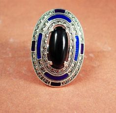 This is a statement art deco style ring like no other. It is LARGE ( setting is 1 1/2 long) and fabulous and solid sterling with inlaid guilloche blue enamel, marcasites and a large Onyx center stone. MUCH nicer than the photo and a real high quality piece of jewelry. And remember, a personal well thought out gift shows you took the time to care about that special person in your life. Our items are classic, sometimes unusual and vintage and sometimes a little bizarre. Whether it is a mem...