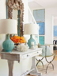 loving this beach house decor, so coastal living, shell mirror, blue lamps with white shades, lovely rustic side table and a pop of colour with orange flowers, yum to beach cottage style