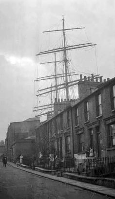 Deptford Ferry Road Britannia Dock - Street view in Ferry Road off West Ferry Road. Above the terraced houses the masts and yards of the barque Killoran can be seen under repair in Britannia Dry Dock. Linney (Museum of London ) Victorian London, Vintage London, Old London, South London, Victorian Life, City Of London, London Style, London Pictures, Old Pictures