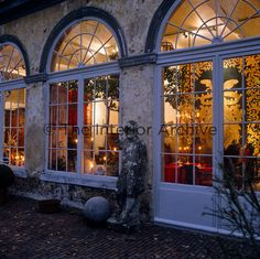 A view through the fanlight windows of the candlelit garden room furnished with tapestries and crystal chandeliers