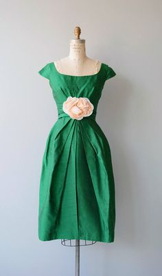 Vintage 1950s green raw silk party dress with wide neckline, cap sleeves, gathered bodice, fitted waist, large silk flower at the waist, slight bubble skirt and metal zipper. --- M E A S U R E M E N T S --- fits like: small bust: 36 waist: 26 hip: 42 length: 42 brand/maker: Neli-Fran