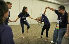 Students race to pass a hula hoop around each other while holding hands as they play cooperative games while participating in the Building Leaders And Strong Tomorrows Youth Group Games, Team Games, Youth Activities, Team Building Activities, Family Games, Activity Games, Fun Games, Games For Kids, Youth Groups