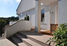 WPC Terrasse mit Stufen vor moderner Villa bei Sonnenschein