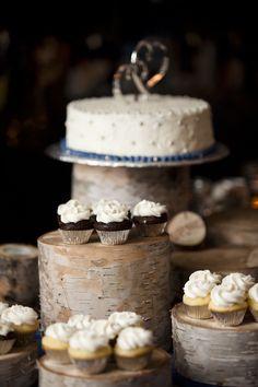 Un assortiment de desserts sur des gros morceaux de tronc d'arbre de différentes hauteurs.