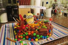 Easy Minion cake: minion toy and a whole lot of chocolate, candy and lollipops with a homemade message banner for the birthday ba-boy!