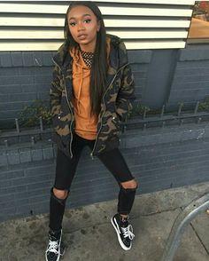 Camo jacket, burnt orange sweater, black ripped jeans, vans