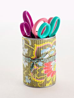 Desk Accessories Holder: Jazz up an old tin can to sit pretty on a desk. Remove labels and clean can. Cut textured decorative paper to the height and width of the can. Wrap the paper piece around the can and adhere it with decoupage medium. Cut a length of coordinating ribbon. Wrap it around the can and tie. I already make a bunch of these, but thought I would share