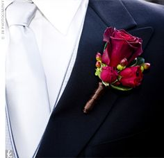 Chris sported a rich cluster of roses and hypericum berries on his lapel