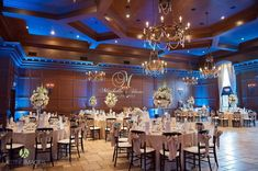 Indoor wedding reception in Firenze ballroom with mahogany chairs, crystal candelabras, iron chandeliers, blue up-lighting, champagne chair ties and linens with white roses and hydrangeas as centerpieces. | Lasting Images Photography| villasiena.cc