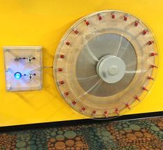 """In this exhibit, a central disk with multiple magnet-tipped arms forms the rotor of a generator. The visitor turns a handle to spin the rotor,. As the magnet-tipped arms of the rotor pass the electromagnets, electricity is generated in the coils. LEDs at each coil light up to show when it is producing power. The visitor can also """"see"""" the electricity produced by switching on a light bulb and/or fan connected to the generator."""