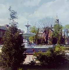 Spring time at The Nelsonville, Ohio Public Square featuring the Fountain and the Central School Building in the 1950s
