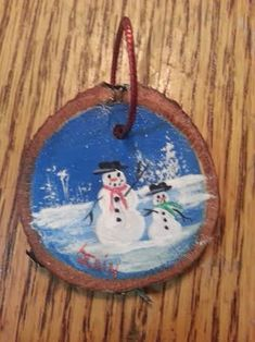 My husband cut this wood slice for me from a piece of oak. I hand painted two snowmen in acrylic and sealed it with a sealer. It has a red twine