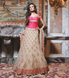PEACH & GOLD A-LINE OUTFIT  W065  Striking coral corset with flamoyant lengha, fully netted. Skirt has net layer over a brocade motif embroidered layer.  COLLECTION  Wedding - Autumn 2010  COLOUR  Coral & Gold  FABRIC  Top – Raw silk  Skirt - Brocade/Net  Dupatta – Net