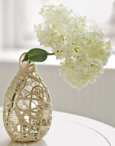 VASE Tightly wrap a doily around a vase. Snip away any excess, then hand-stitch the doily securely in place to create a snug fit.