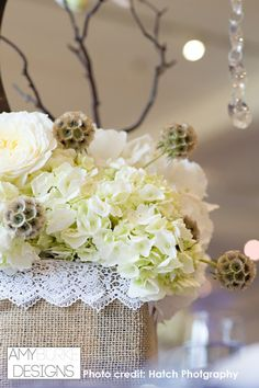 White Hydrangea, Scabiosa Pods, and branches with crystals as a low centerpiece. #neutral