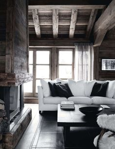high gloss black flooring and coffee table. reclaimed wood celings and awesome fireplace. Brought together with clean white sofa and some black accent pillows.