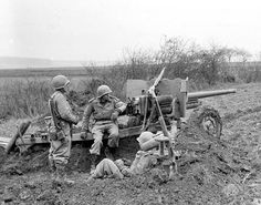 Artillerymen from the 12th Armored Division take a break next to their 57-mm…